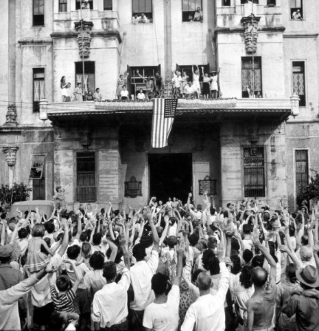 Carl Mydans. American flag draped over balcony of building as American and Filipino civilians cheer their release from the Japanese prison camp at Santo Tomas University folllowing Allied liberation of the city. Manila, Luzon, Philippines. February 05, 1945