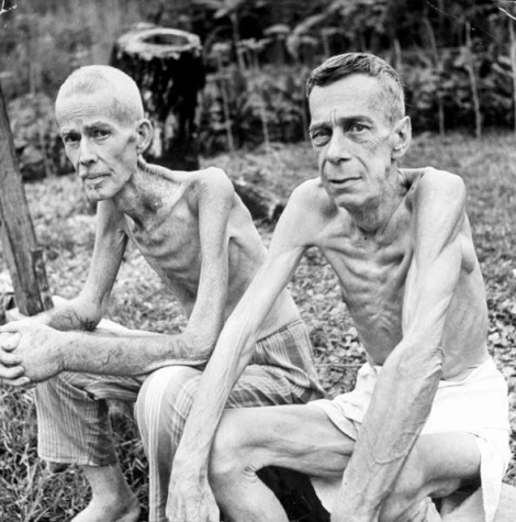 Carl Mydans. Two emaciated American civilians, Lee Rogers (L) & John C. Todd, sit outside gym which had been used as a Japanese prison camp following their release by Allied forces liberating the city. Manila, Luzon, Philippines, February 05, 1945