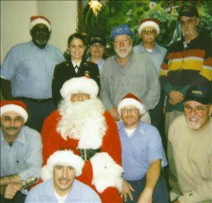 "Santa with VVGSQ members and supporters. San Quentin Prison visiting room - December 18, 2005. The VVGSQ has always supported the San Quentin Christmas Toy Program with toy donations as well as by running the program each year. The Warden has authorized the VVGSQ to sponsor this program and the group purchased the ""Santa"" suit, beard and wig that is used for an appearance of Santa to the children each year at the visiting room. The program benefits all the children who come to visit family at San Quentin during the Christmas season. Started in 1988, December 2008 will be the 20th year the program has been giving toys to the children who visit San Quentin."