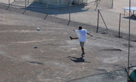 A detainee kicks a soccer ball around the central recreation yard at Camp 4, Joint Task Force (JTF) Guantánamo Bay, Cuba, June 10, 2008, during his daily outdoor recreation time. Detainees in Camp 4 get up to 12 hours of daily of outdoor recreation, including two hours in a central recreation yard. Photo Credit: U.S. Army 1st Lt. Sarah Cleveland