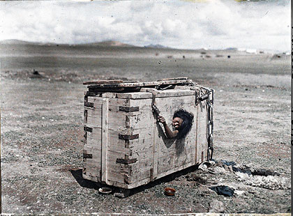 Stéphane Passet. Mongolian prisoner in a box, July 1913. Image courtesy of BBC. © Musée Albert Kahn