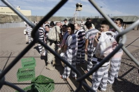 Approximately 200 convicted illegal immigrants handcuffed together arrive at their new part of the jail as they are moved into a separate area of Tent City, by orders of Maricopa County Sheriff Joe Arpaio, for incarceration until their sentences are served and they are deported to their home countries Wednesday, Feb. 4, 2009, in Phoenix. (AP Photo/Ross D. Franklin)