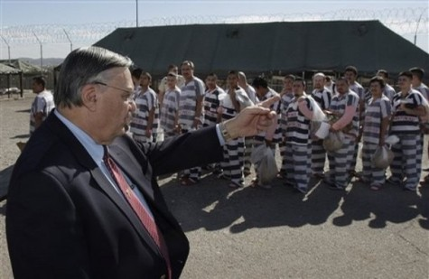 Maricopa County Sheriff Joe Arpaio, left, orders approximately 200 convicted illegal immigrants handcuffed together and moved into a separate area of Tent City, inmates behind Arpaio, for incarceration until their sentences are served and they are deported to their home countries Wednesday, Feb. 4, 2009, in Phoenix. (AP Photo/Ross D. Franklin)