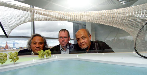 (L-R) Anish Kapoor, Joe Docherty, Chief Executive of Tees Valley Regeneration, and Cecil Balmond crouch behind a table.