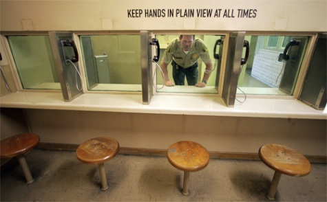 Mel Melcon / Los Angeles Times. VISITING ROOM: L.A. County Sheriff's Deputy Jack McClive peers through safety glass, while standing in the visiting room, during a tour of the Sybil Brand Institute Women's Jail in Monterey Park.