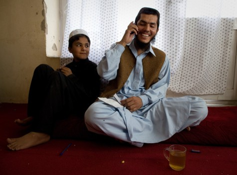 Mohammed Jawad talks on the phone to a friend as a relative looks on in his family home on September 25, 2009 in Kabul, Afghanistan. He was the youngest Guantanamo Bay prisoner only 17 when he was arrested six years ago, but his lawyer says he was 14 and family members say he was 12. JawadÕs conviction was for throwing a hand grenade at two U.S. soldiers. The judge said his confession was obtained under torture. © Paula Bronstein/Getty
