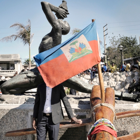 "A pilgrim touches the Kita Nago, a tree trunk, which became a symbol of national unity, after a journey of two weeks across the country. Statue of the ""Unknown Maroon"" Champ de Mars, City of Port-au-Prince"