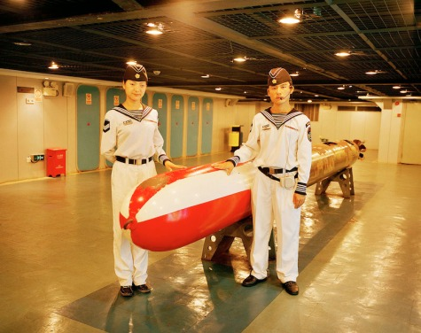 "China, Shenzhen;  Empoyees with Torpedo on the Themepark ""Minsk World"". The Aircraft Carrier was built in the 70s by the Russians. After that it was sold to the Chinese in the late 90s, who decided to bring the Ship from Russia to China to restore it and"