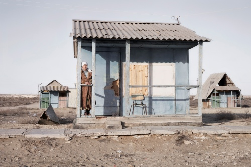 Past of Kenderli. 2011 A women stays near her house in abandoned soviet holiday camp at Kenderli beach. Current the camp is demolished and soon will become a luxury resort with planned 6 billion dollars investments. Kazakhstan. 2011