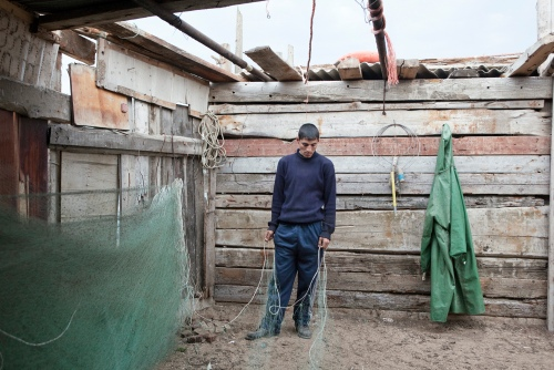 Fisherman with his nets. 2010 Fisherman gathers his nets in a poaching hut at Pirallahi island. As no other work exists outside the capital, people living along the sea are turning to the poaching, which is largely covered by bribes. The Caspian Sea is overfished for years, and the sturgeon is currently close to complete extinction. Azerbaijan, 2010