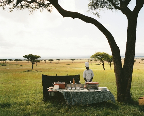 A chef from a nearby luxury lodge waits for his guests to arrive from a hot air balloon excursion before serving them champagne in the middle of the Maasai Mara National Reserve, Kenya. 2012 Guillaume Bonn
